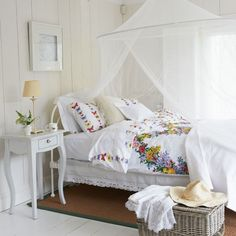 White country bedroom  A voile net has been hung above the bed for a cool air of romance. Floral bedlinen adds colour as well as keeping the room feminine.
