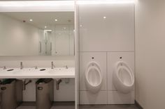 Bespoke bright white Corian vanity unit incorporating individual basins with inset soap dispensers and concealed waste bins.