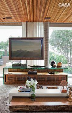 A TV, instalada num tubo de metal, gira 180 graus. O rack de madeira e vidro foi executado pela Móveis Donizete.Mesa de centro da Espaço Design.