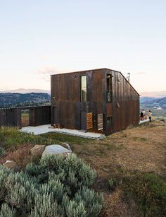 A prefabricated off-the-grid vacation home in eastern Washington provides not just a getaway, but lessons in learning to be one with the land. The steel cladding has developed a patina similar to the ochre-red color of bedrock found in the area.      This originally appeared in Off-the-Grid Prefab Cabin Completely in Tune with Surroundings.