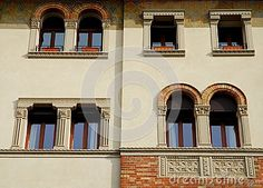 Photo taken at a palace in Treviso in Veneto (Italy). The picture shows a detail of a large and elaborate facade, facing west and sunlit, of an elegant and historical building in the city center. They see a total of three mullioned windows, two arched rectangular windows and two singles.