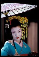 Maiko girl (Geisha apprentice) in blue kimono posing with her umbrella in the Gion quarter of Kyoto, Japan