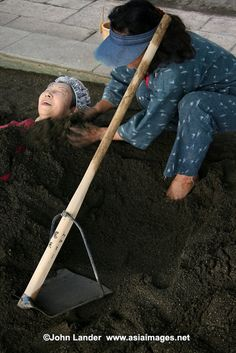 Japanese woman being buried in a sand bath at Beppu, one of the very few places in Japan where sand or mud are also used for spa treatments. Beppu's sand bath is conveniently located on Shoningahama Beach