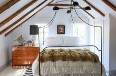 An elegant, swooping iron canopy bed makes the most of the steepled attic ceiling in this petite bedroom.