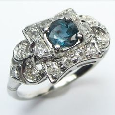 Chameleon Ring: This curvaceous panel top ring holds a delightful and rare, natural, color change sapphire.  In some light it is a lush purple, and in others, a mellow teal.  Ca.1935.  Maloys.com