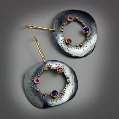 Dotted Pebble Dangles by Wendy Stauffer. Argentium sterling silver is sawed, textured and hammered to form lightly domed pebble shapes. Dots of 18k gold and 14k gold tube set gemstones add lively contrast. The stones include a 4mm amethyst, a 3mm fire citrine and a 3mm rhodolite garnet. The silver is oxidized to a gunmetal gray and given a soft sheen. The pebbles suspend lightly from 14k gold earwires.