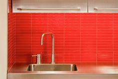 Fantastic red glass tiles and stainless steel cabinets in this kitchen. Discovered on search.porch.com #interiors #interiordesign #decor #red #tiles