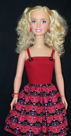 My Size Barbie is pictured here wearing a very cute spaghetti-strap little red dress. The bodice of the dress is crafted from a red cotton and is embellished at the straps with two black little bows. The gathered skirt is also made from a black cotton imprinted with red/pink buttered flies bordered with gold glitter. Pink hearts are everywhere too! Dolls/Doll Jewelry/Accessories/Doll Shoes Not Included.  $21 - www.etsy.com/shop/sewdollycute