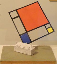 """Piet Mondriaan is gekozen tot de beroemdste Amersfoorter aller tijden. Daarom is aan drie kunstenaars gevraagd een ontwerp voor een monument voor hem te maken, dat herinnert aan zijn eerste acht levensjaren die hij in Amersfoort doorbracht. De Russische kunstenaar Andrei Roiter gaat uit van het geboortehuis waar de stempel van Mondriaan opgedrukt zit. Het schilderij """"Compositie met rood, geel en blauw"""" uit 1930 is als een boemerang die door de lucht vliegt en terugkaatst op het huis."""