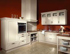 Landelijke witte keuken in een roestbruine ruimte. Deze keuken steekt door de gekozen kleur prachtig af tegen de achtergrond. Er zijn verschillende soorten keukenkastjes voorzien voor het opbergen van het kookmateriaal.