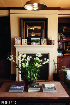 Cindy Crawford's gorgeous living space with a grand flower arrangement, industrial lighting, and marble fireplace