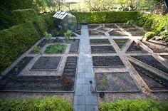 En smuk køkkenhave med gennemgående flisegang fra kompost indgangen. Dog spejlvendt for, at passe til aspargesene