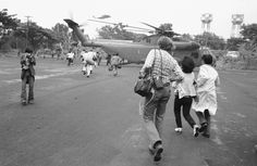 Americans and Vietnamese run for a U.S. Marine helicopter in Saigon during the evacuation of the city, April 30, 1975