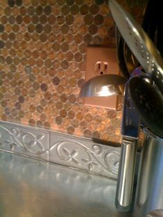 The Mama Crow: Copper Penny Backsplash- love the tile just below the pennies too.    Adhere pennies to a cloth mesh such as used for needlepoint.  Adhere the mesh to the wall and grout the pennies.