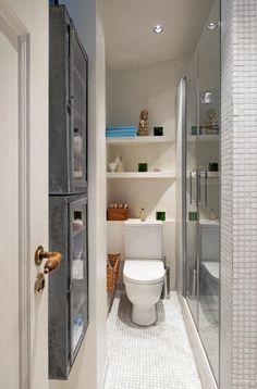 Ide til bad i 1.etg: Plassen er godt utnyttet på det smale badet, ved hjelp av åpne hyller over toalettet og smale skap. Badesonen befinner seg bak glassdørene til høyre.