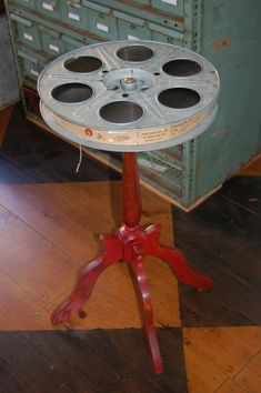 Side table made from vintage movie reel  Still has film. Green table in Loft. Need glass top.  Use old film reel.