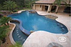 Free form pool that features a fountain and hot tub.