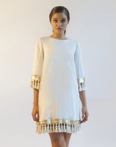 Shimmy, shimmy and shake! We were captivated by our mothers' vintage photographs of the Philippines in the 1960s when designing this mod-inspired white cocktail dress with gold tassels at the hem and
