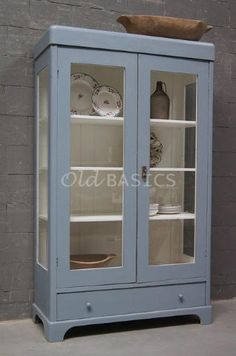 Oude houten vitrinekast in een grijze kleur. Deze kast heeft door de twee glazen zijkanten een luchtige uitstraling. De binnenkant is wit van kleur en onderin zit een lade.