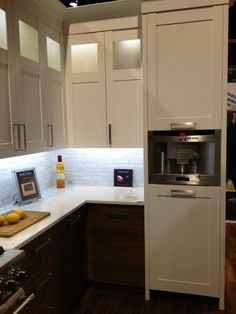 Built-in espresso machine, white upper cabinets with lights behind glass panel