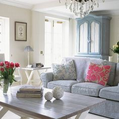 French-style living room.  Farrow & Ball-painted walls are a backdrop for a blue sofa with Jane Churchill covers and a blue cabinet lined with antique fabric. A limed coffee table displays flowers, books and carved decorative balls. A blue gingham lampshade, striped French armchairs and floral cushions add pattern contrast. Tulips, a Designers Guild hot pink cushion and a chandelier add glamour.