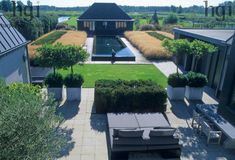 Harpur Garden Images Ltd :: ppbo29 Contemporary garden with large paved area, seating, containers of topiarised trees, long water feature with garden building as focal point. Mass grass planting around water. aerial views pots planters lifestyle Design: (Planting) Piet Oudolf. Owner and architect Piet Boon. Contemporary Formal Dining Paving Grasses Hedges Lawns Metal containers Minimalist overview Naturalistic Seating Topiary Water Holland. Jerry Harpur Please read our licence terms. All…