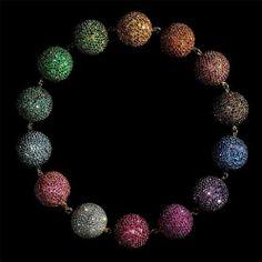 (© Copyright Briti... Nova-iorquino do Bronx, Rosenthal mudou-se para Paris logo após a formatura na Universidade de Harvard, em 1966. Na capital francesa, ao lado de Pierre Jeannet, iniciou a carreira de designer de joias. Este colar, de 1999, é uma mistura de rubis, safiras, esmeraldas, ametistas, turmalinas, diamantes, prata e ouro, entre outros materiais. (Foto: 'Colored Balls Necklace'/ Jozsef Tari. Cortesia de JAR, Paris)