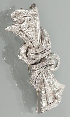 ART DECO DIAMOND SET BROOCH. Formed by two dress clips on a frame, the diamond set knotted motif set with diamonds totalling very approximately 2.00 carats, unmarked, possibly platinum. #ArtDeco #DoubleClip #brooch