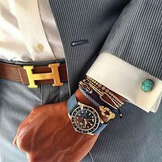 Pinstriped suit paired with a classic Hermes belt and colorful cuff links and watch.