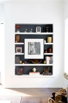 Painted interior of shelf. Bookshelf with artwork mounted in the middle