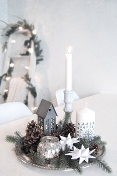 silver plate a couple of pine cones and candles and quaint church for a perfect centerpiece