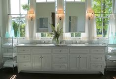 Bathroom with mirror in front of windows. Room Details: Hardwood floors continue into the master bath as homage to the historic folk style, as do the mirrors hung in front of windows. Countertop is Bianco Carrara marble.  Julie Couch Interiors. Picture by The Decorlogista.