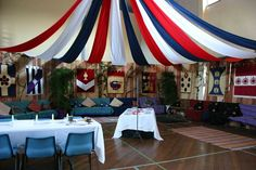 Decorating and Gym or other rented space as a Medieval Hall - heraldic banners and themes are a key component. After set up, all you need to do is turn out the lights and use candle light for an immersive environment (the hanging streamers shadow and therefore hide the non-theme ceiling in the candle light). Follow link to see the whole set up and the final look in the candle light - Amazing. http://threegoldbees.com/projects/7-hall-decorating-in-the-sca