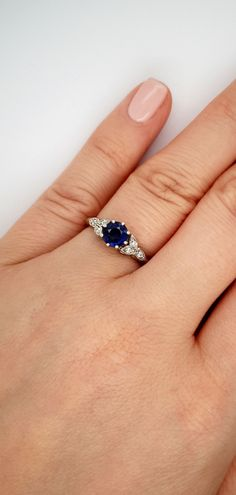 Inspired by a floral aesthetic, the round royal blue sapphire is highlighted by three diamond-set leaves on either side of the main gemstone. The ring features a high D-shape band and is made in our workshop in Hatton Garden, London. #LondonVictorianRing #HattonGarden #SapphireRing #SapphireEngagementRing #BlueSapphire #FloralRingDesign Engagement Rings On Finger, Floral Engagement Ring, Designer Engagement Rings, Saphire Ring, Blue Sapphire Rings, Diamond Rings With Price, Diamond Wedding Rings, Country Rings, Hatton Garden