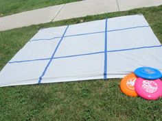 Frisbee Tic Tac Toe -            shower curtain from Dollar Tree and we used cheap tape (also from Dollar Tree) to make a Tic Tac Toe grid.  Then we set 6 frisbees out and t...