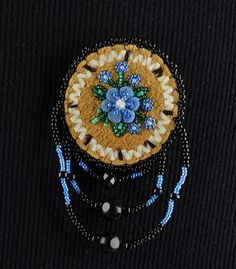 Moose Hide Tufted Pin. Beaded with blue, green and colored beads into a flower shaped caribou tufted hair in the center, with black colored beads around the edging. There is porcupine quills around the outside of the flowers. Corinna M. Evans, Athabascan