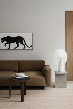 Modern and minimal living room interior with brown sofa and white table lamp