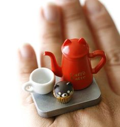 Super Cute!!!! Coffee pot in a cat shape with a mug and cute cat shape cupcake!!    It measures approx. 1.25 inch wide and 1.45 inch high is on a silver plated adjustable bang that will fit most ring sizes.