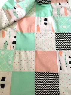 Perfect for your little girls nursery or a great gift for a new baby. The feather quilt is a patchwork quilt made with a variety of fabrics including cute feather fabric, 2 different mint cotton fabrics, black & white chevron, coral and white dot fabric, gold, mint & coral triangles fabric and your choice of soft minky dimple dot fabric on the back. Minky options are mint, white, & coral. The feather baby blanket is a great gift for newborns, infants and toddlers.   DETAILS  ✂ Fea...