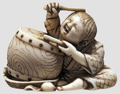 Ivory Netsuke Japan in 1900, Fully shaped and finely carved netsuke in the form of a drum beating boy with engraved and blackened details. The underside with lacquer inlaid signature. Length of 4 cm.