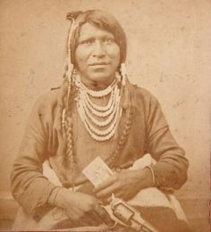 """Rare and original, 1870's Native American Ute Indian Stereoview Photograph of a brave by the name of """"Indian Charley"""" holding a rather large revolver in one hand and a cabinet card photograph in the other. The Photograph was taken by the famous Mormon Photographer Charles R. Savage of Salt Lake City, Utah"""
