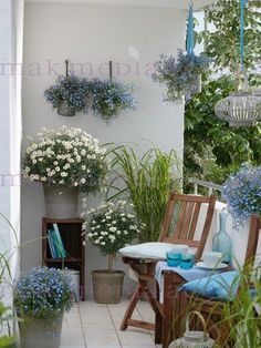 cozy balcony with potted small flowers and folding chairs - Small Balcony - Balkon