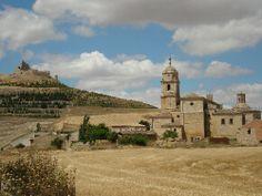 les ruines du château se découpent sur le ciel bleu au somment de la motte castrale Au pied de la colline, le village et l'église de Notre Dame du Manzano (du pommier). Cette configuration des villages espagnols remontent à ...