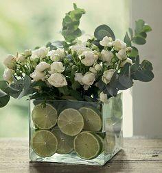Arranjo de flores em vidro decorado com fatias de limao