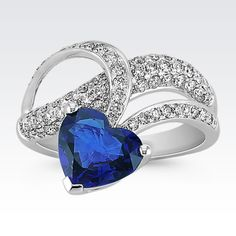 The look of love is vibrant in this stunning ring as part of our exclusive One-Of-A-Kind collection. One bold heart-shaped sapphire, at 2.32 carats, hangs down in quality 14 karat white gold. Add in 79 round diamonds, at .77 carat TW, and you have an extremely eye-catching design. The total gem weight is 3.09 carats.