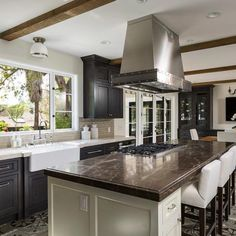 Traditional style with Mediterranean touches? Yes, please! 😍  Brown marble, ivory island cabinetry with drawer storage, mosaic cement tile floor, black perimeter kitchen cabinets, and gray stone countertops -- what more do you need for a dream to come true?   📷 by Van Parys Architecture + Design  #traditionalkitchen #traditionalkitchens #classickitchen #classickitchendesign #cabinetshop #woodcabinets #nothingordinary #kitchendesign #kitchen #kitchencabinets #home #vogueliving #kitchenlove