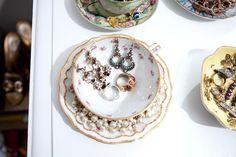 using tea cups to keep jewelry luxuriously organized.  sweet idea.