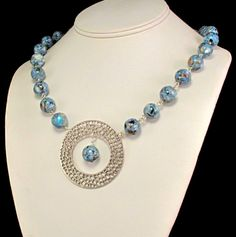 This necklace features a beautiful, silver pendant suspended from a strand of beads which are a composite of many colors, but with blue being the main color. It measures 19 inches long and the round pendant is 1 3/4 inches in diameter. Other necklaces in my shop: https://www.etsy.com/shop/bybrendaelaine?show_panel=true&section_id=6724219  I design and handcraft each piece of my jewelry. I can easily modify many of my items to suit your style and size. I love to hear your ideas and would…