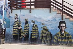 A building mural on San Martin street in Ushuaia depicts a haunting tale of the town's prison history. Explore Ushuaia on foot for a deeper appreciation of its unique culture.