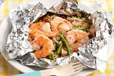 A zesty mix of green beans, rice and sun-dried tomatoes is bundled with shrimp in foil packets on the grill for a tasty dish with easy cleanup.